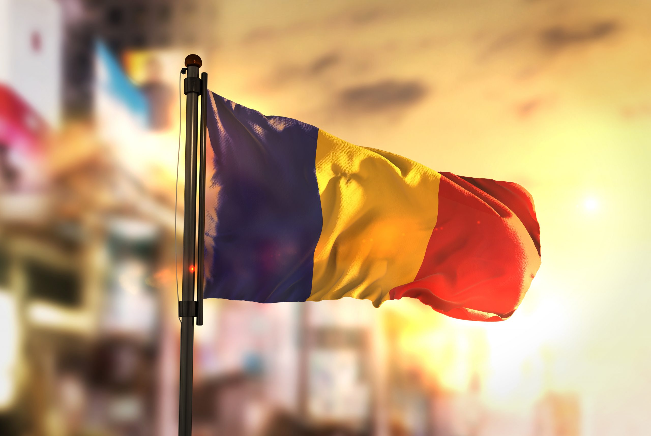 Romania Flag Against City Blurred Background At Sunrise Backlight